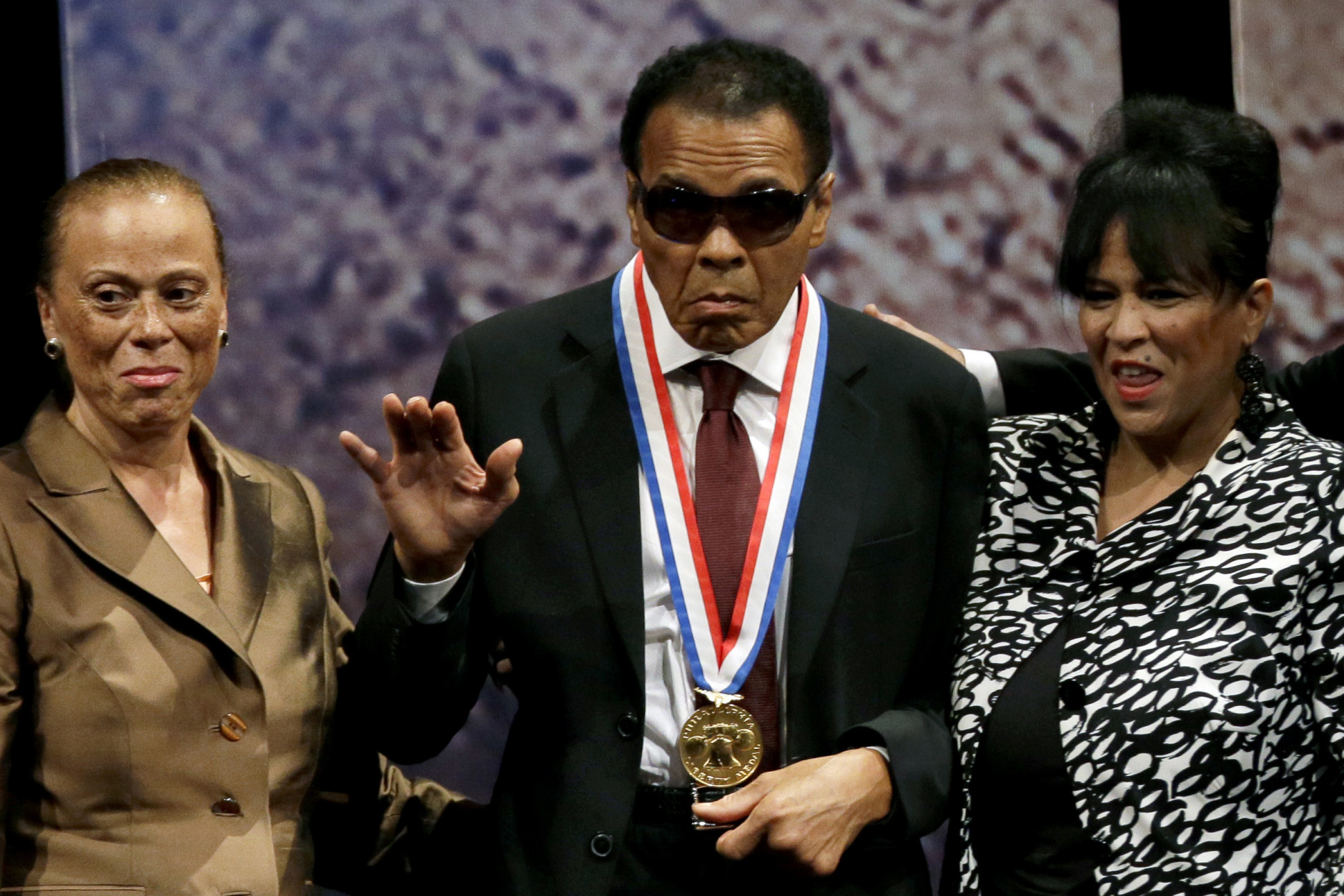 FILE - In this Sept. 13, 2012, file photo, retired boxing champion Muhammad Ali, center, waves alongside his wife Lonnie Ali, left, and his sister-in-law Marilyn Williams, right, after receiving the Liberty Medal during a ceremony at the National Constitution Center in Philadelphia.  Ali, the magnificent heavyweight champion whose fast fists and irrepressible personality transcended sports and captivated the world, has died according to a statement released by his family Friday, June 3, 2016. He was 74. (AP Photo/Matt Slocum, File)