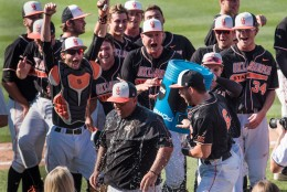 Oklahoma State players celebrate a win over South Carolina by dumping the ice cooler on head coach Josh Holliday at an NCAA college baseball tournament super regional game Sunday, June 12, 2016, in Columbia, S.C. (AP Photo/Sean Rayford)