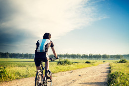 Cyclist Riding a Bike on the Country Road. Rear View. Summer Nature Background. Healthy Lifestyle Concept. Instagram Styled Toned and Filtered Photo. Copy Space.