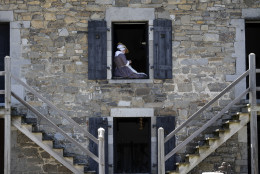 In this Friday, June 17, 2016 photo an historical interpreter tailors trousers in a window of barracks at Fort Ticonderoga in Ticonderoga, N.Y. While the fort also serves as a museum for one of the largest collections of Colonial-era military artifacts, its emphasis has shifted from static exhibits to interpretations of daily life for soldiers in this 18th century wilderness outpost. (AP Photo/Mike Groll)