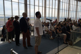 Residents line up to comment about airport noise as planes noisily take off behind them at Reagan National Airport. (WTOP/Michelle Basch)