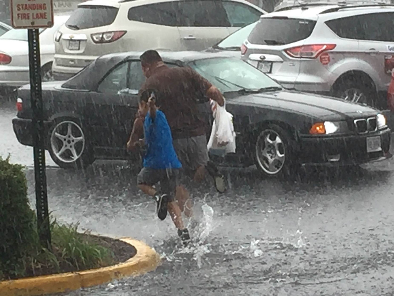 People run to their vehicles in Falls Church, Virginia during storms on June 21, 2016. (Courtesy Larry Rubenstein)