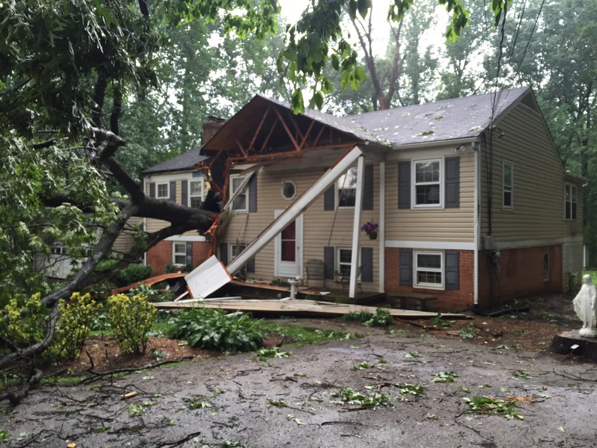 A tree sliced through a home on Burntwoods Road in Glenelg, Maryland, during storms Tuesday. The homeowner's children were home at the time, but both are safe. (WTOP/Michelle Basch)
