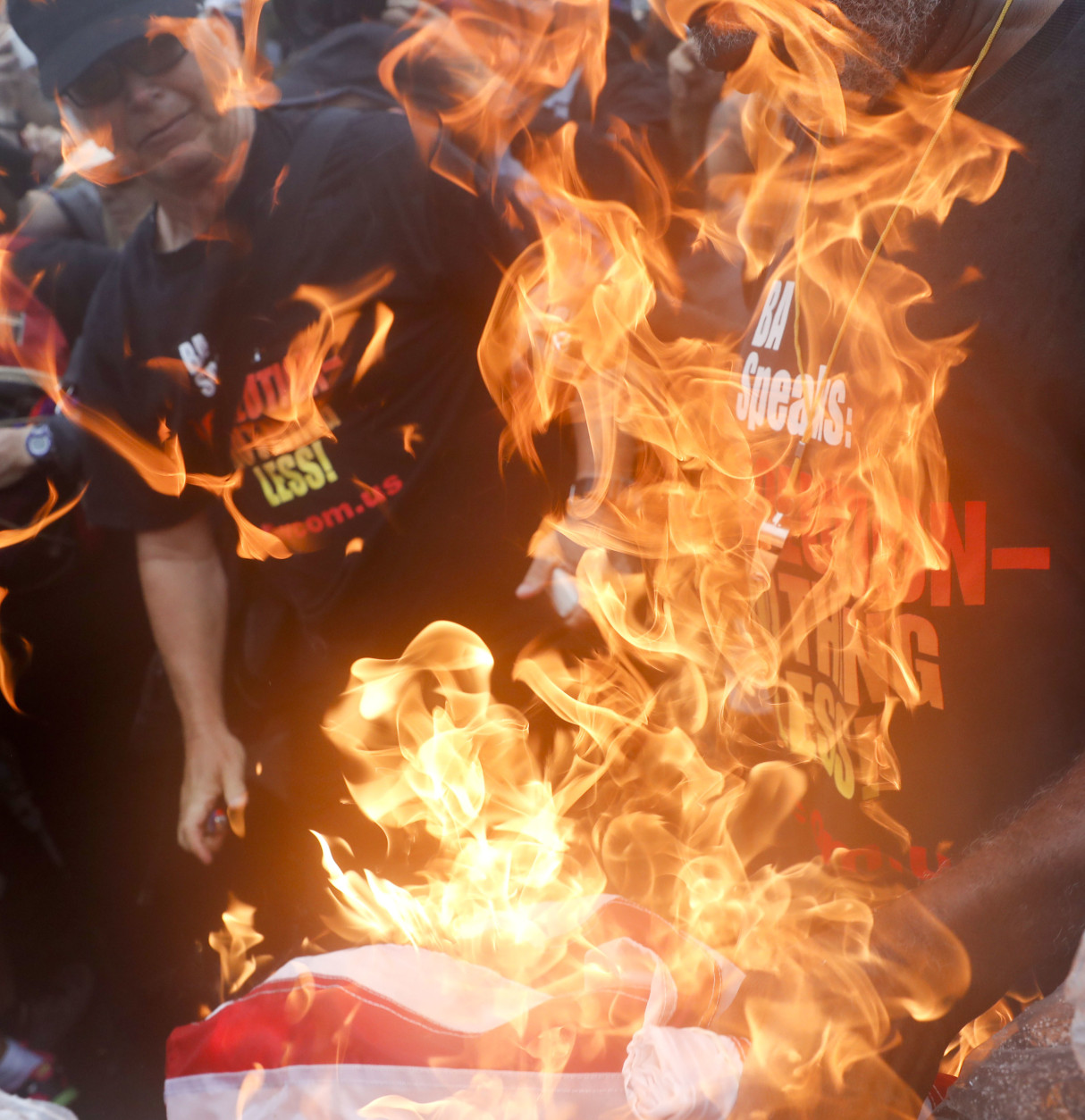"Gregory ""Joey"" Johnson, left, lights an American flag on fire during a protest in Philadelphia, Thursday, July 28, 2016, during the final day of the Democratic National Convention. (AP Photo/John Minchillo)"