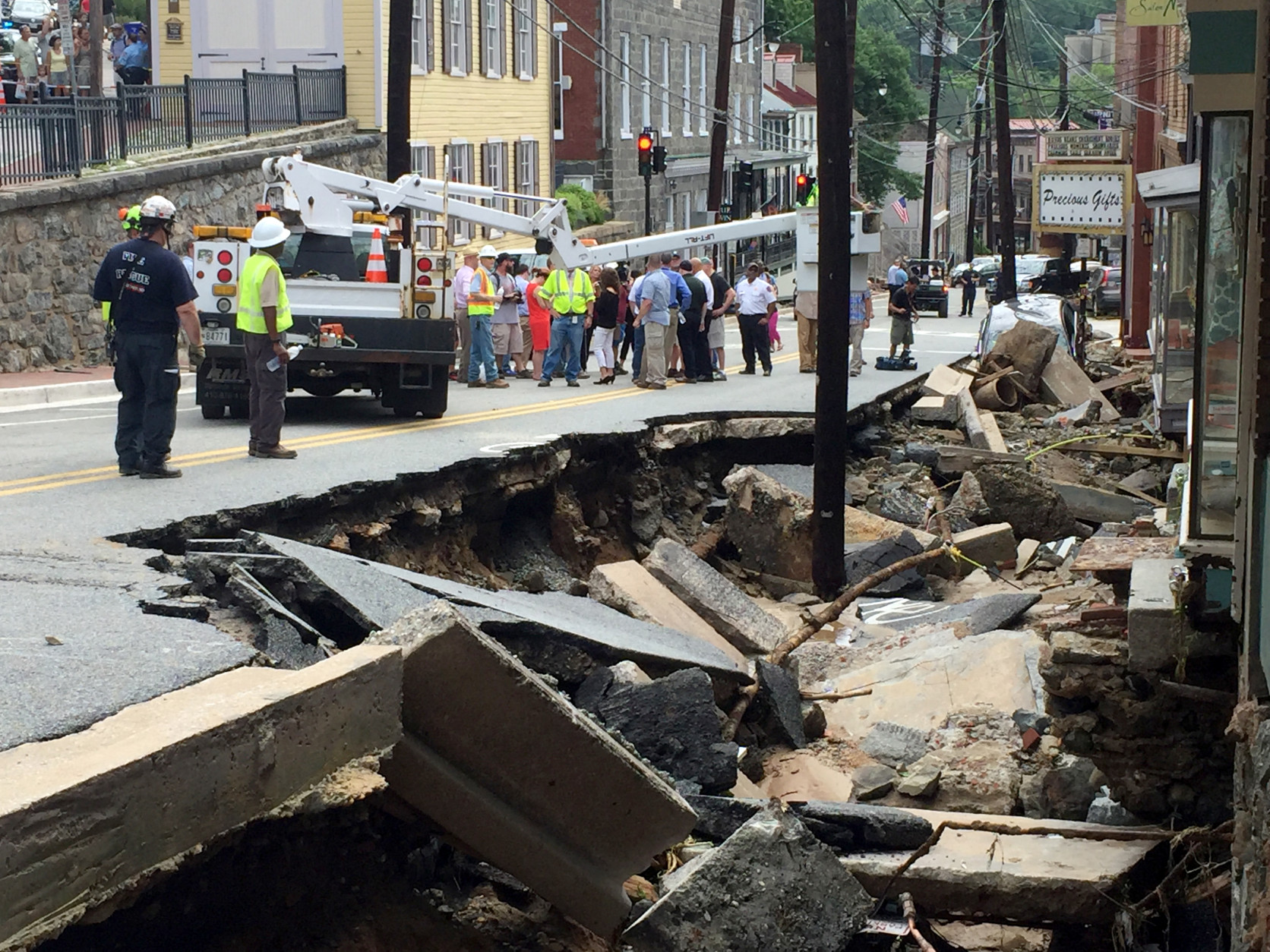 Workers gather by street damage after Saturday night's flooding in Ellicott City, Md., Sunday, July 31, 2016. Historic, low-lying Ellicott City, Maryland, was ravaged by floodwaters Saturday night, killing a few people and causing devastating damage to homes and businesses, officials said. (Kevin Rector/The Baltimore Sun via AP)