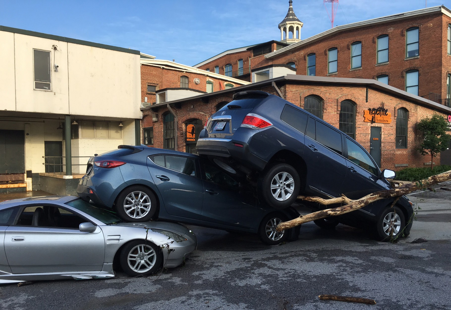 Cars are piled on top of each other in the Meadow Mill parking lot along the Jones Falls in Baltimore on Sunday, July 31, 2016, following Saturday night's storms. (Jerry Jackson/The Baltimore Sun via AP)