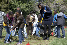 First lady Michelle Obama takes part in groundbreaking of the White House Kitchen Garden on the South Lawn of the White House of the White House in Washington, Friday, March 20, 2009, with students from Washington's Bancroft Elementary School. (AP Photo/Ron Edmonds)