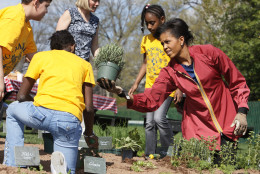 First lady Michelle Obama plants herbs on the White House Kitchen Garden with students from Bancroft Elementary School in Washington, Thursday, April 9, 2009, on the South Lawn of the White House in Washington. (AP Photo/Charles Dharapak)