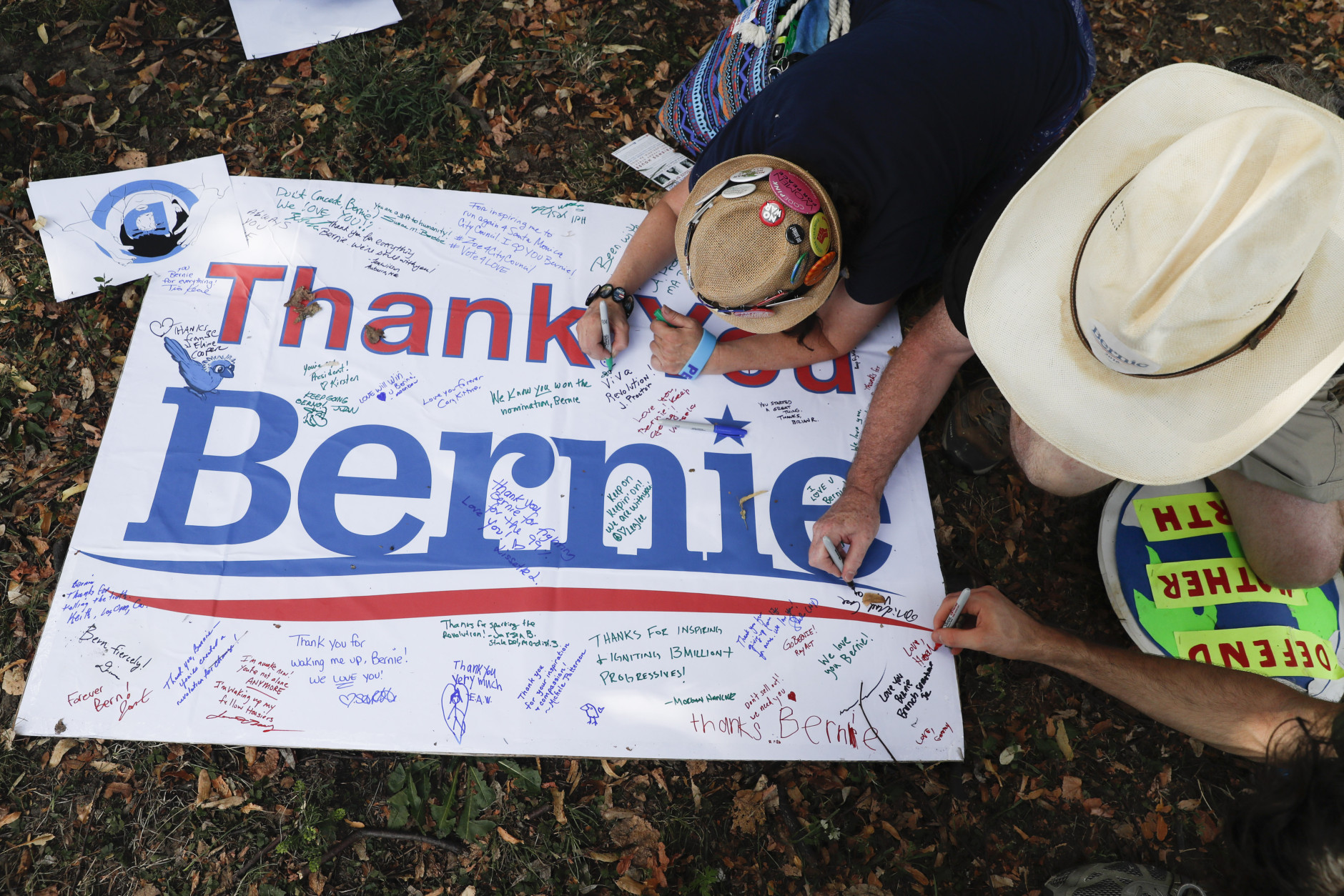 Supporters of Sen. Bernie Sanders, I-Vt., write comments on a sign following a protest march through downtown on Sunday, July 24, 2016, in Philadelphia. The Democratic National Convention starts Monday in Philadelphia. (AP Photo/John Minchillo)