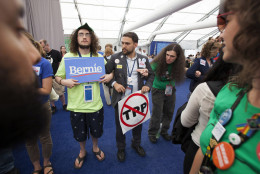 Supporters of Bernie Sanders delegate Nina Turner lock arms during protest inside the media tent on Wednesday, July 27, 2016, the third day of the Democratic National Convention in Philadelphia. They say she's being punished by the party for her support of Sanders. (AP Photo/Michael R. Sisak)