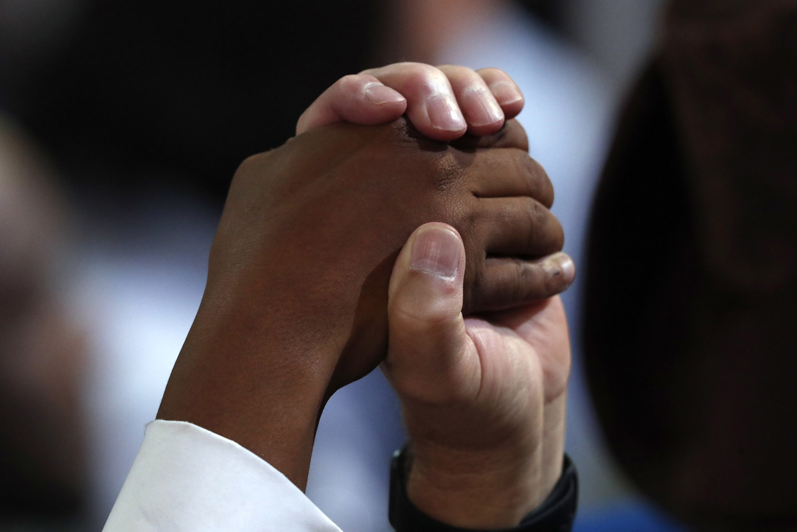 Two people join hands during the closing benediction on the final day of the Democratic National Convention in Philadelphia, Thursday, July 28, 2016. (AP Photo/Paul Sancya)