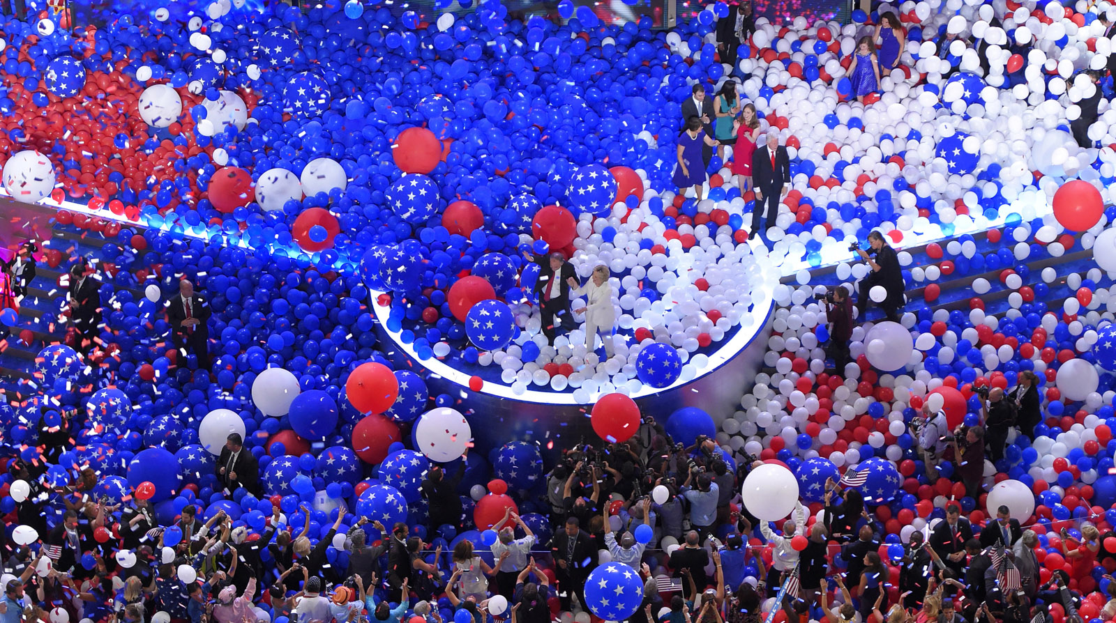 Democratic vice presidential nominee Sen. Tim Kaine, D-Va., and Democratic presidential nominee Hillary Clinton waves to supporters as balloons s the balloons fall during the final day of the Democratic National Convention in Philadelphia , Friday, July 29, 2016. (AP Photo/Mark J. Terrill)