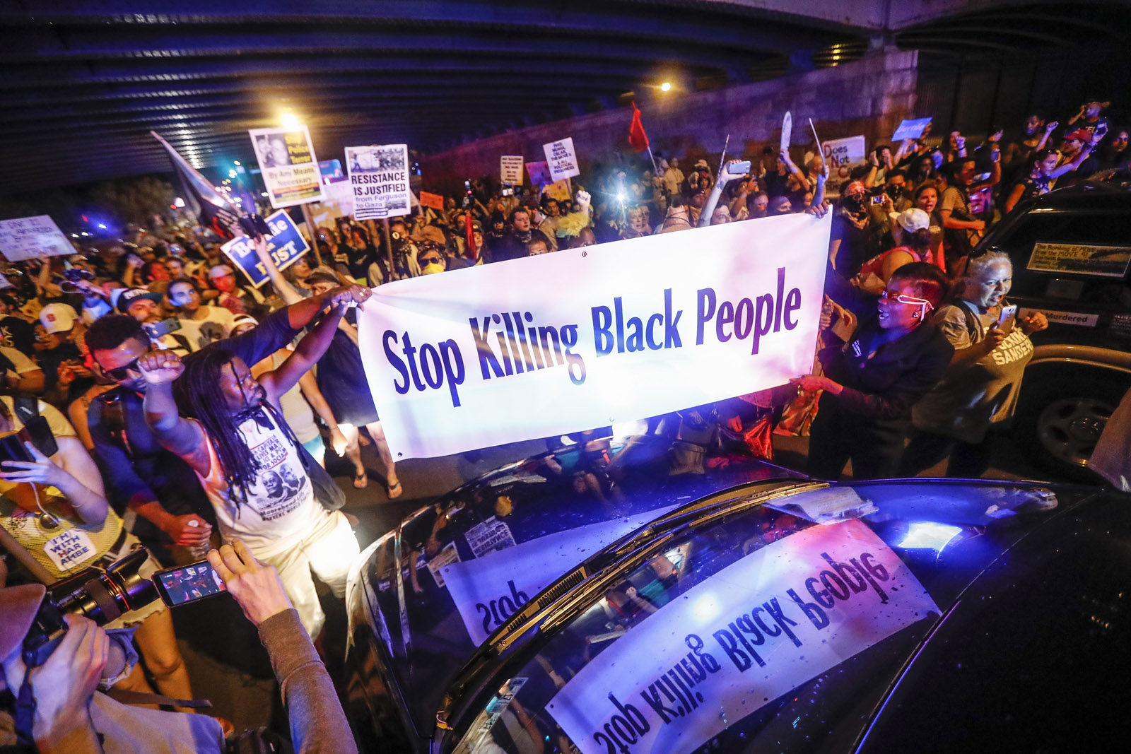 Black Lives Matter demonstrators gather at the police vehicle stuck facing northbound during a protest march south on Broad Street in Philadelphia, Tuesday, July 26, 2016, during the second day of the Democratic National Convention. (AP Photo/John Minchillo)