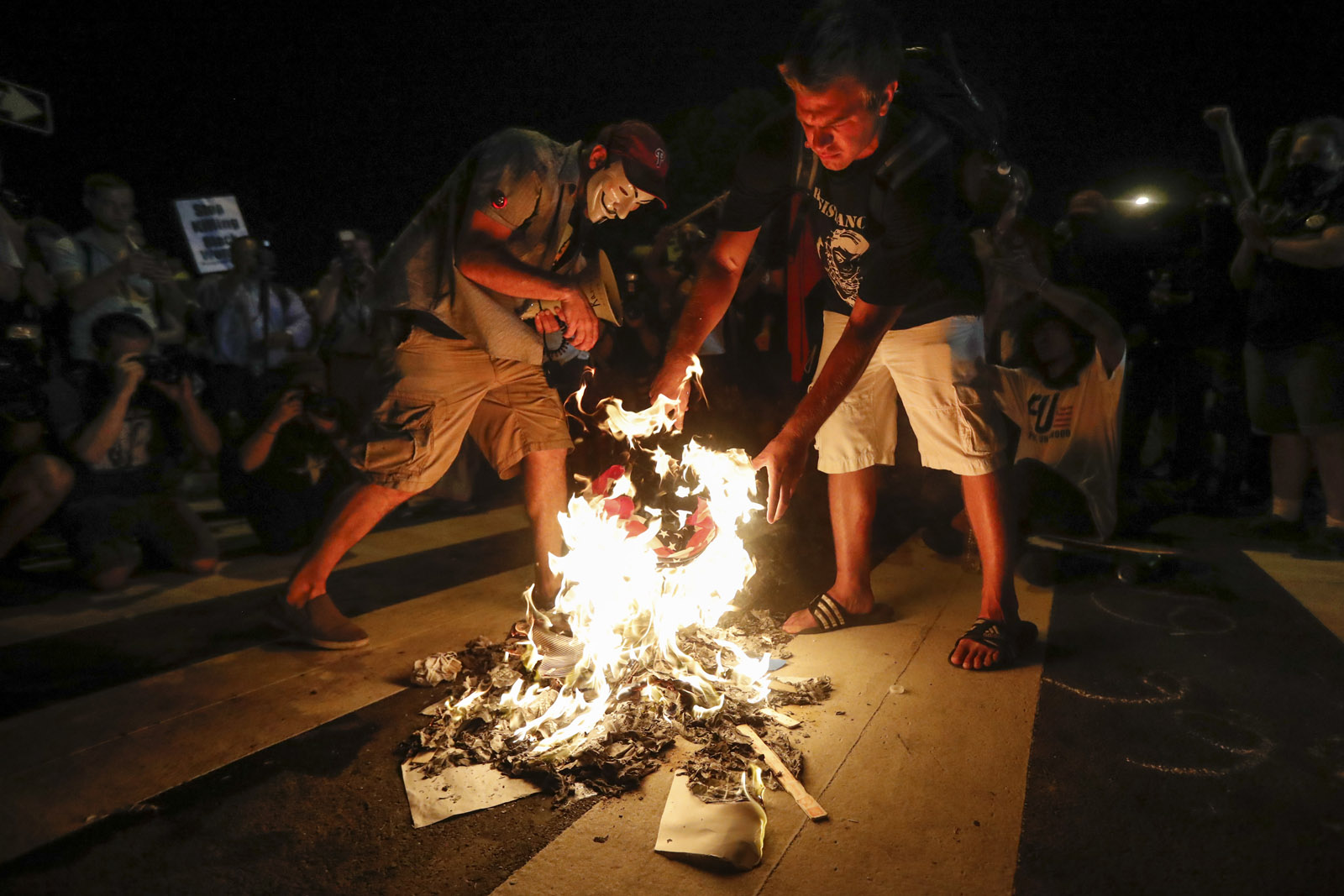 Demonstrators burn an American flag during a protest in Philadelphia, Tuesday, July 26, 2016, during the second day of the Democratic National Convention. (AP Photo/John Minchillo)