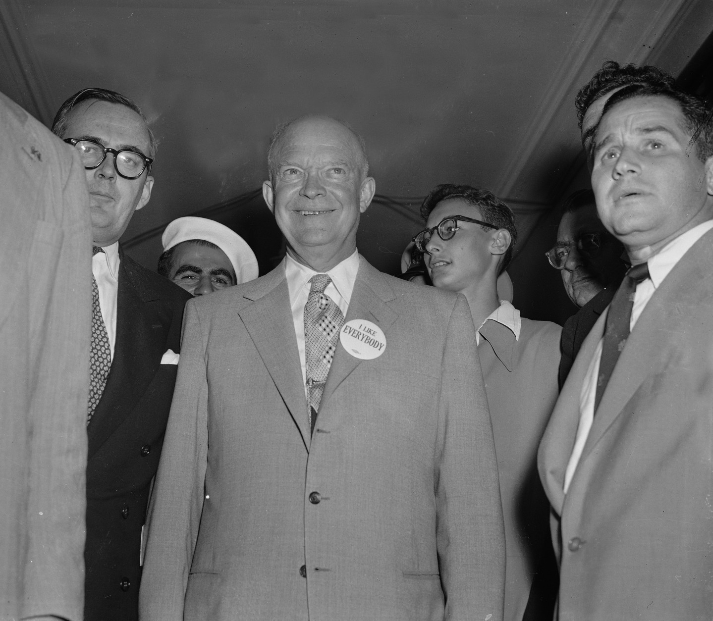 "Republican presidential candidate Dwight D. Eisenhower, beaming and happy, wears an ""I Like Everybody,"" pin on his coat lapel before leaving his hotel for the convention hall in Chicago, July 11, 1952, where the Republican National Convention is being held.  Others are unidentified.  (AP Photo)"
