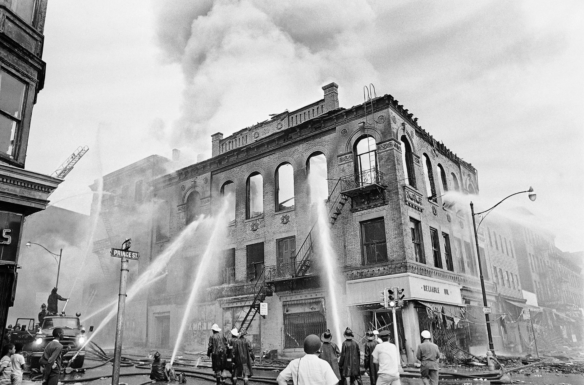 Newark firemen play steady streams of water on gutted structure at Court and Prince Streets in Newark, N.J., July 15, 1967. Three days of burning and violence have cost the New Jersey city 11 dead and hundreds wounded. (AP Photo/Marty Lederhandler)