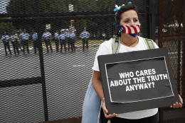Demonstrators picket a fence as police stand guard during a protest at Franklin Delano Roosevelt park, Thursday, July 28, 2016, in Philadelphia. (AP Photo/John Minchillo)