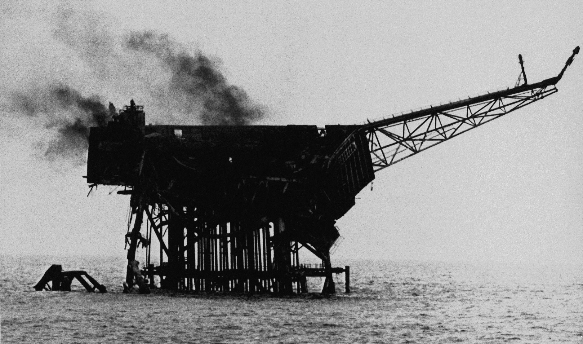 Smoke rises from the burnt out shell of the Piper Alpha oil platform in the North Sea off the coast of Aberdeen, Scotland, July 7, 1988. More than 150 oil rig workers died, when the rig exploded and caught fire Wednesday night. (AP Photo)