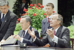 U.S. President George H. Bush gestures while President Nursultan Nazarbayev of Kazakhstan reads his papers after signing a nonproliferation treaty in the Rose Garden of the White house in Washington, Tuesday, May 19, 1992. President Nazarbayev said Tuesday that his country will adhere to agreements barring the transfer of nuclear weapons and their technology. (AP Photo/Ron Edmonds)