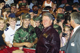 Wearing a leather jacket inscribed with his name and title and given to him by local personnel, President Bill Clinton meets with members of the American Armed Forces gathered at the Ramstein Air Force Base in Berlin, July 11, 1994. In a speech, President Bill Clinton promised there would be no further cuts in defense spending and that U.S. troops would remain in Europe. (AP Photo/Marcy Nighswander)
