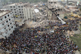 FILE - In this April 25, 2013, file photo, Bangladeshi people gather as rescuers look for survivors and victims at the site of a building that collapsed a day earlier, in Savar, near Dhaka, Bangladesh. The bloody weekend attack by Bangladeshi militants that left more than two dozen dead has also dealt a deadly blow to the country's vital garment industry. Clothing manufacturing, the Southeast Asian nation's top export industry, had been recovering after a disastrous factory collapse three years ago shook up the industry, forcing workshops producing for foreign brands to improve working conditions. (AP Photo, File)