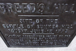 "In this Tuesday, June 28, 2016 photo, an historic plaque noting the location of ""Breed's Hill"" is fixed to the side of a building next to the Bunker Hill monument, which is located on Breed's Hill in the Charlestown neighborhood of Boston. The Battle of Bunker Hill, one of the greatest misnomers in U.S. history, is being waged anew on social media. The 1775 battle, a pivotal rallying point for American colonists trying to overthrow British rule, actually was fought on Breed's Hill, not Bunker Hill. (AP Photo/Charles Krupa)"