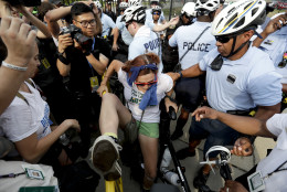 A demonstrator is taken into custody by police after climbing over a barricade near the AT&T Station, Monday, July 25, 2016, in Philadelphia, during the first day of the Democratic National Convention. (AP Photo/Matt Slocum)