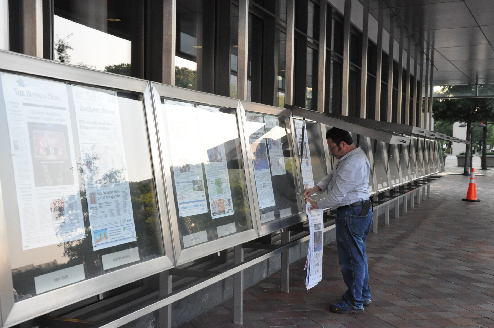 Every morning, Mike Machado prints and hangs the front pages of newspapers from the U.S. and across the world outside the Newseum on Pennsylvania Avenue. (WTOP/Rachel Nania)