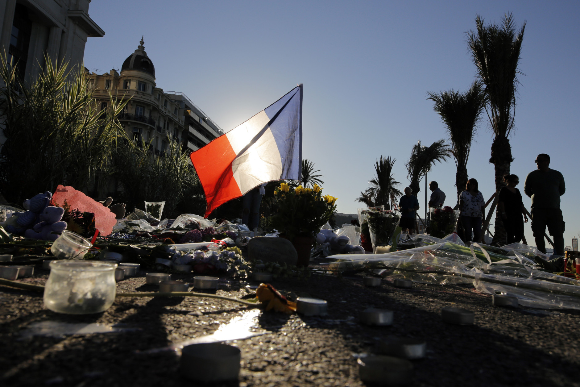 FILE - In this Sunday, July 17, 2016 file photo, a French flag stands stall amongst a floral tribute for the victims killed during a deadly attack, on the famed Boulevard des Anglais in Nice, southern France. The relentless series of mass killings across the globe poses a challenge for experts trying to analyze them without lapsing into faulty generalizations. Terms like contagion and copycat killing apply in some cases, not in others, they say, and in certain instances perpetrators' terrorist ideology intersects with psychological instability. (AP Photo/Laurent Cipriani, File)