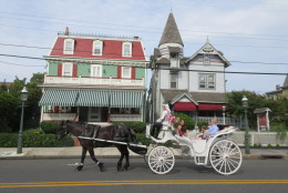 "This June 26, 2015 photo shows visitors taking a horse carriage tour of Cape May, N.J. The city's hundreds of Victorian homes constitute what the National Historic Landmarks program calls ""one of the largest collections of 19th century frame buildings"" in the United States. Their gables, towers, domes, arched windows and inviting front porches, often trimmed in bright colors, create charming and whimsical streetscapes.  (AP Photo/Beth J. Harpaz)"