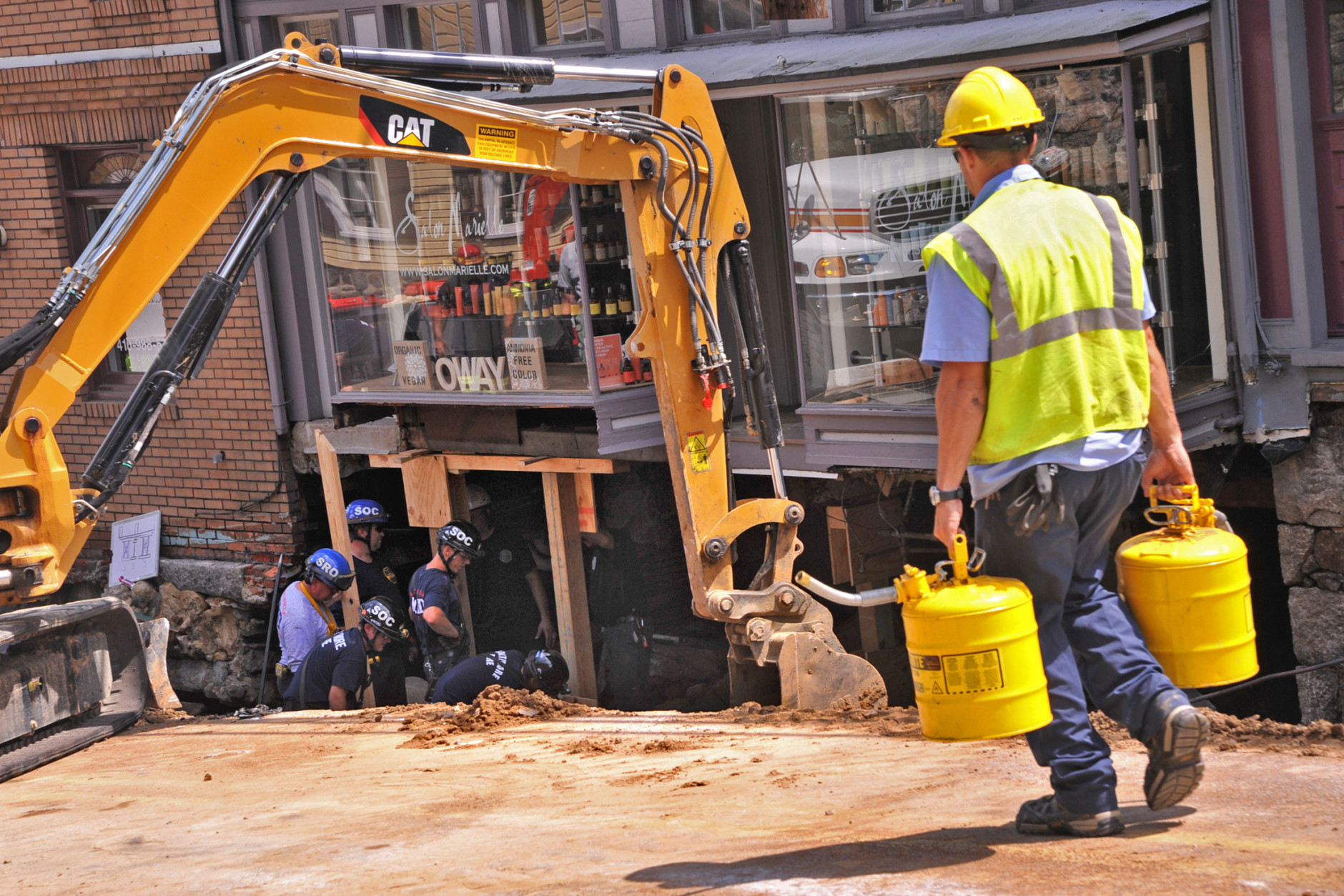Workers stabilize a building on Main Street after the sidewalk caved in due to overnight flooding in Ellicott City, Md., Sunday, July 31, 2016. Historic, low-lying Ellicott City, Maryland, was ravaged by floodwaters Saturday night, killing a few people and causing devastating damage to homes and businesses, officials said. (Amy Davis/The Baltimore Sun via AP)