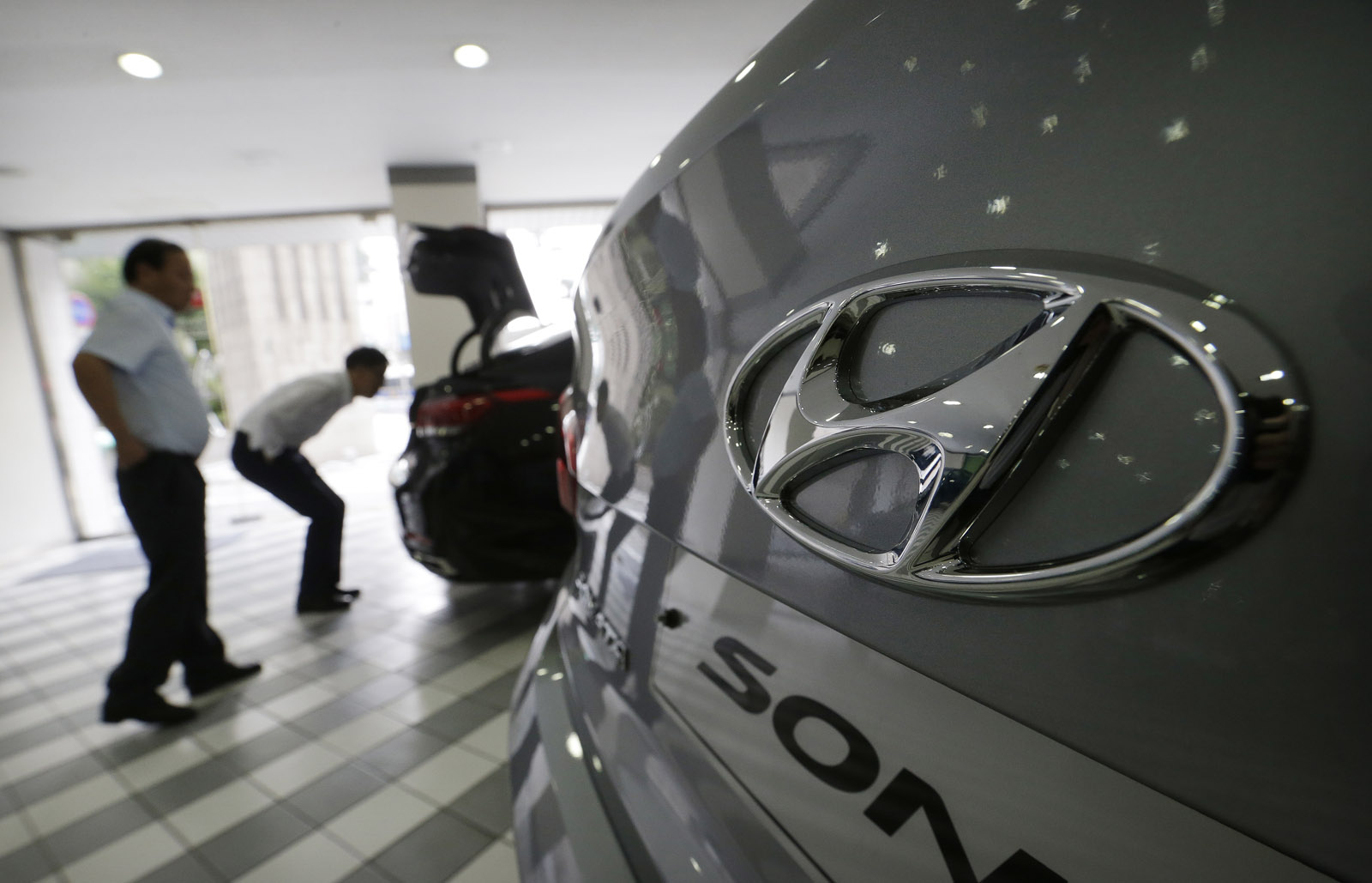 The logo of Hyundai Motor Co. is seen on a vehicle displayed at the company's showroom in Seoul, South Korea, Tuesday, July 26, 2016. Hyundai Motor Co. says its second-quarter income fell from a year earlier for a tenth straight quarter.(AP Photo/Ahn Young-joon)