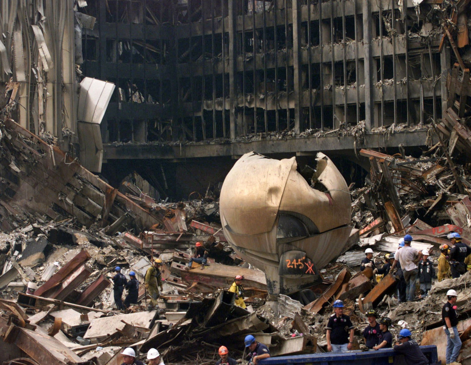 """FILE - In this Sept. 24, 2001 file photo, Fritz Koenig's """"The Sphere"""" outdoor sculpture that once graced the plaza at New York's World Trade Center lies in the wreckage following the Sept. 11, 2001, terrorist attacks. The 25-ton, bronze sphere ripped open by the collapsing towers is returning to a spot overlooking the rebuilt site. The Port Authority of New York and New Jersey on Thursday July 21, 2016, approved plans to move the Koenig Sphere from its temporary place in Battery Park at Manhattan's southern tip. The sculpture will grace the new Liberty Park overlooking the 9/11 memorial. No date has yet been set for the move. (AP Photo/Ted Warren, Pool/File)"""