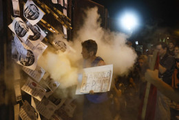 "A demonstrator is enveloped in a cloud of fire extinguisher as fliers stuck into a police barricade bearing ""Bernie or Bust"" logos burn near AT&T Station during a protest in Philadelphia, Tuesday, July 26, 2016, during the second day of the Democratic National Convention. (AP Photo/John Minchillo)"