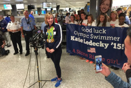 Flanked by fans and well-wishers at Dulles International Airport, Olympic swimmer Katie Ledecky answers questions from the media. (WTOP/Katie Ledecky)