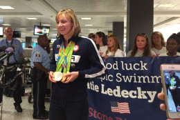 Five-time Olympic gold medalist Katie Ledecky displays her medals for the media at Dulles International Airport after returning from Rio. Ledecky says fellow U.S. swimmer Michael Phelps taught her how to display her medals. (WTOP/Kristi King)