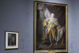 """People view weapons near a portrait of King George III in the """"Peace, Liberty, and Independence"""": 225 Years After the Treaty of Paris exhibit at the Pennsylvania Academy of the Fine Arts in Philadelphia, Wednesday, Sept. 10, 2008.  The new exhibit tracks the course of the second-longest conflict in U.S. history the American Revolutionary War and the ways art helped rally support for independence from the British and promote the values of the emerging republic. (AP Photo/Matt Rourke)"""