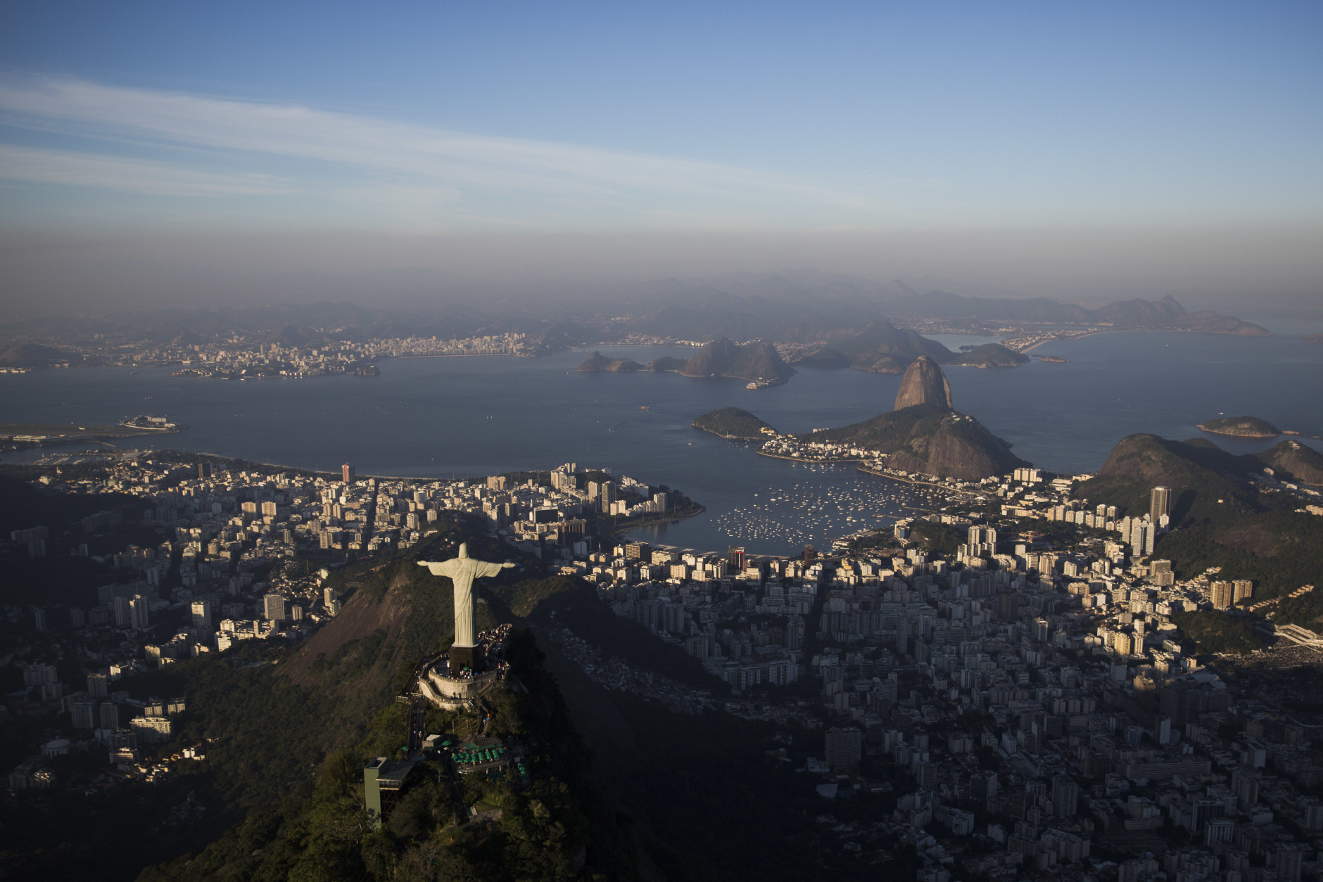 The Sugar loaf and Guanabara bay are seen behind the Christ the Redeemer statue in Rio de Janeiro, Brazil, Monday, July 4, 2016. With the Olympics set to start on Aug. 5, the games and the city have been overshadowed by security threats, violence, the Zika virus and a national political corruption scandal. (AP Photo/Felipe Dana)