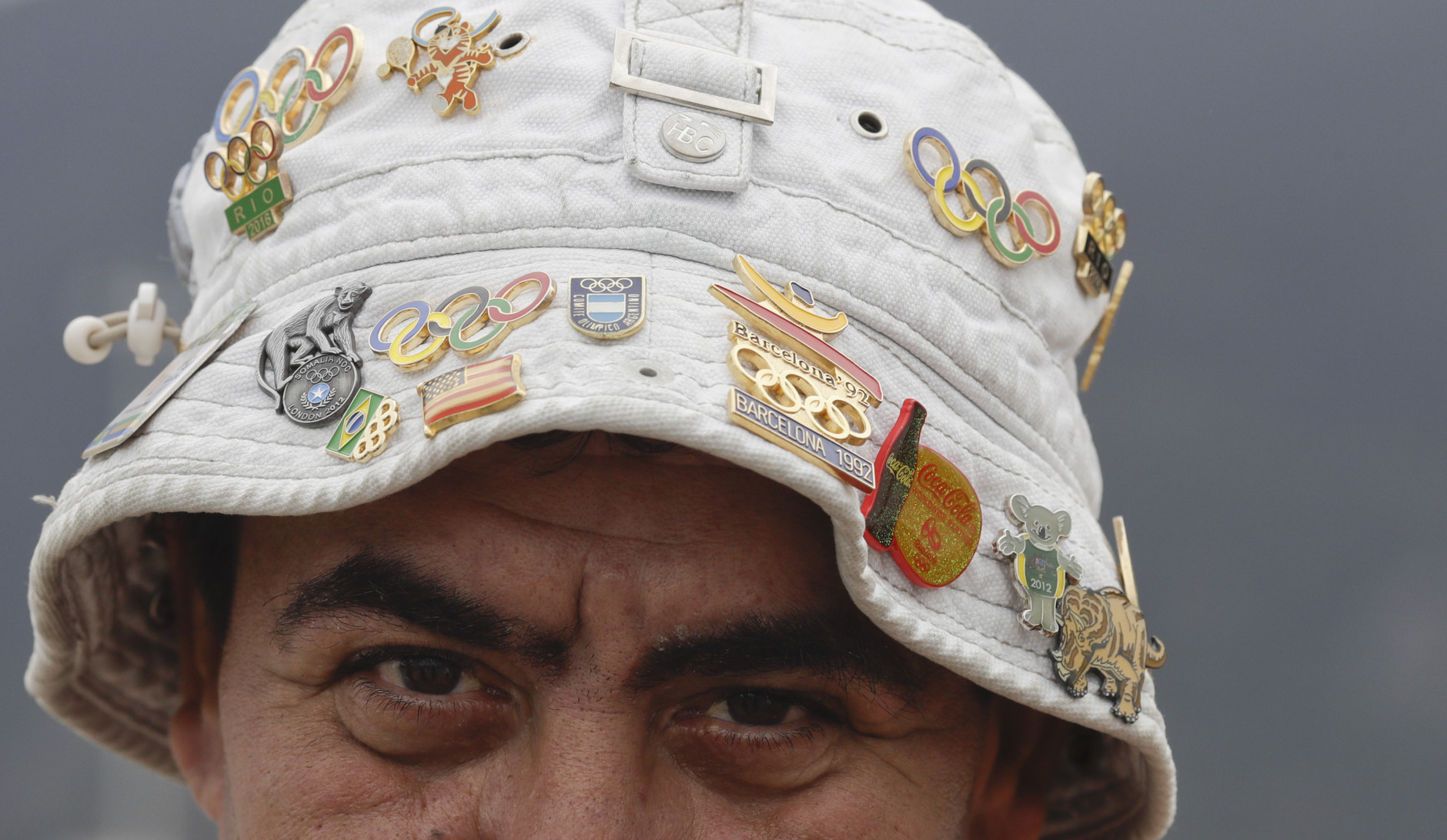 A man wearing a hat with pins poses for a picture outside the Olympic village ahead of the 2016 Summer Olympics in Rio de Janeiro, Brazil, Wednesday, Aug. 3, 2016. The Games opening ceremony is on Friday.(AP Photo/Natacha Pisarenko)