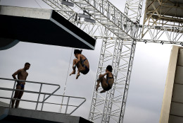 Divers are seen in silhouette as they take part in a training session in the Maria Lenk Aquatic Center ahead of the 2016 Summer Olympics in Rio de Janeiro, Brazil, Wednesday, Aug. 3, 2016. (AP Photo/Wong Maye-E)