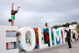 "Yves Karrer, of Switzerland, does a handstand atop a sign the reads ""Cidade Olimpica"" or ""Olympic City"" outside the Museu do Amanha ahead of the upcoming 2016 Summer Olympics in Rio de Janeiro, Brazil, Wednesday, Aug. 3, 2016. (AP Photo/David Goldman)"