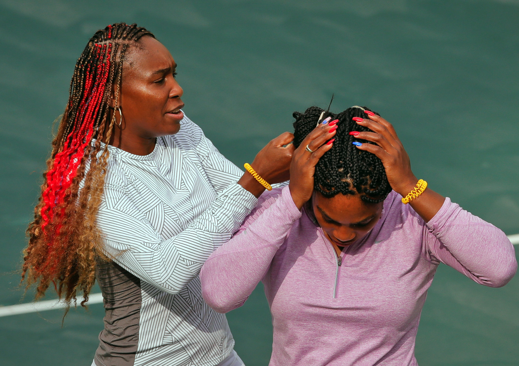 Venus Williams of the United States, left, helps her sister Serena Williams adjust her hair before a practice session on the central court ahead of the upcoming 2016 Summer Olympics in Rio de Janeiro, Brazil, Wednesday, Aug. 3, 2016. (AP Photo/Vadim Ghirda)