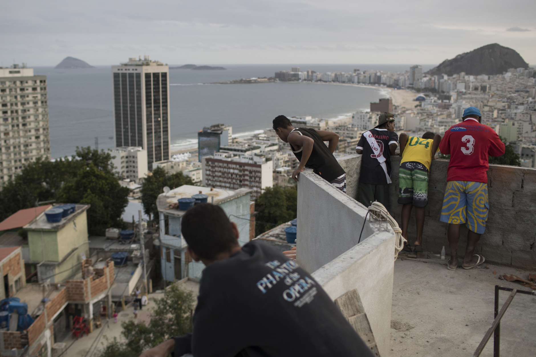 Boys look at kites atop the Babilonia slum, overlooking Copacabana beach in Rio de Janeiro, Brazil, Wednesday, Aug. 3, 2016. The Olympics are scheduled to open Aug. 5. (AP Photo/Felipe Dana)