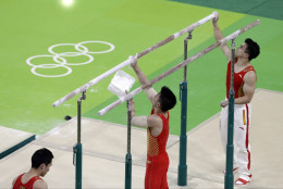Members of the Chinese gymnastics team prepare the parallel bars before a training session ahead of the 2016 Summer Olympics in Rio de Janeiro, Brazil, Wednesday, Aug. 3, 2016. (AP Photo/Rebecca Blackwell)