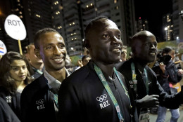 Members of the Refugee Olympic Team walk back to their apartments after a welcome ceremony at the Olympic athletes village in Rio de Janeiro, Brazil, Wednesday, Aug. 3, 2016. The Summer 2016 Olympics is scheduled to open Aug. 5. (AP Photo/Charlie Riedel)