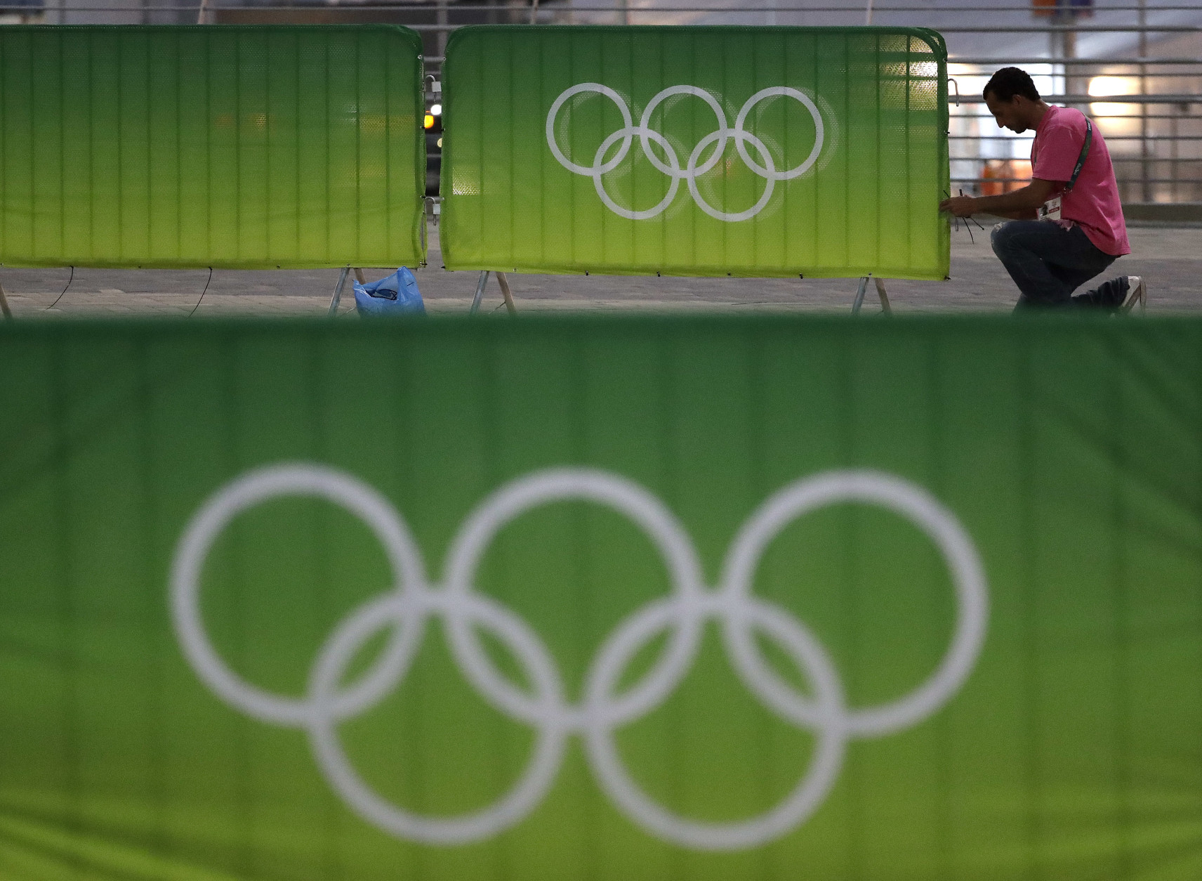 A worker fastens signage to a barrier in the Olympic Park as preparations continue for the Summer 2016 Olympics in Rio de Janeiro, Brazil, Wednesday, Aug. 3, 2016. The Summer 2016 Olympics is scheduled to open Aug. 5. (AP Photo/Charlie Riedel)