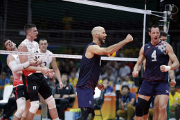 United States' William Reid Priddy, center, and David Lee, right, celebrate during a men's preliminary volleyball match against Canada at the 2016 Summer Olympics in Rio de Janeiro, Brazil, Sunday, Aug. 7, 2016. (AP Photo/Jeff Roberson)
