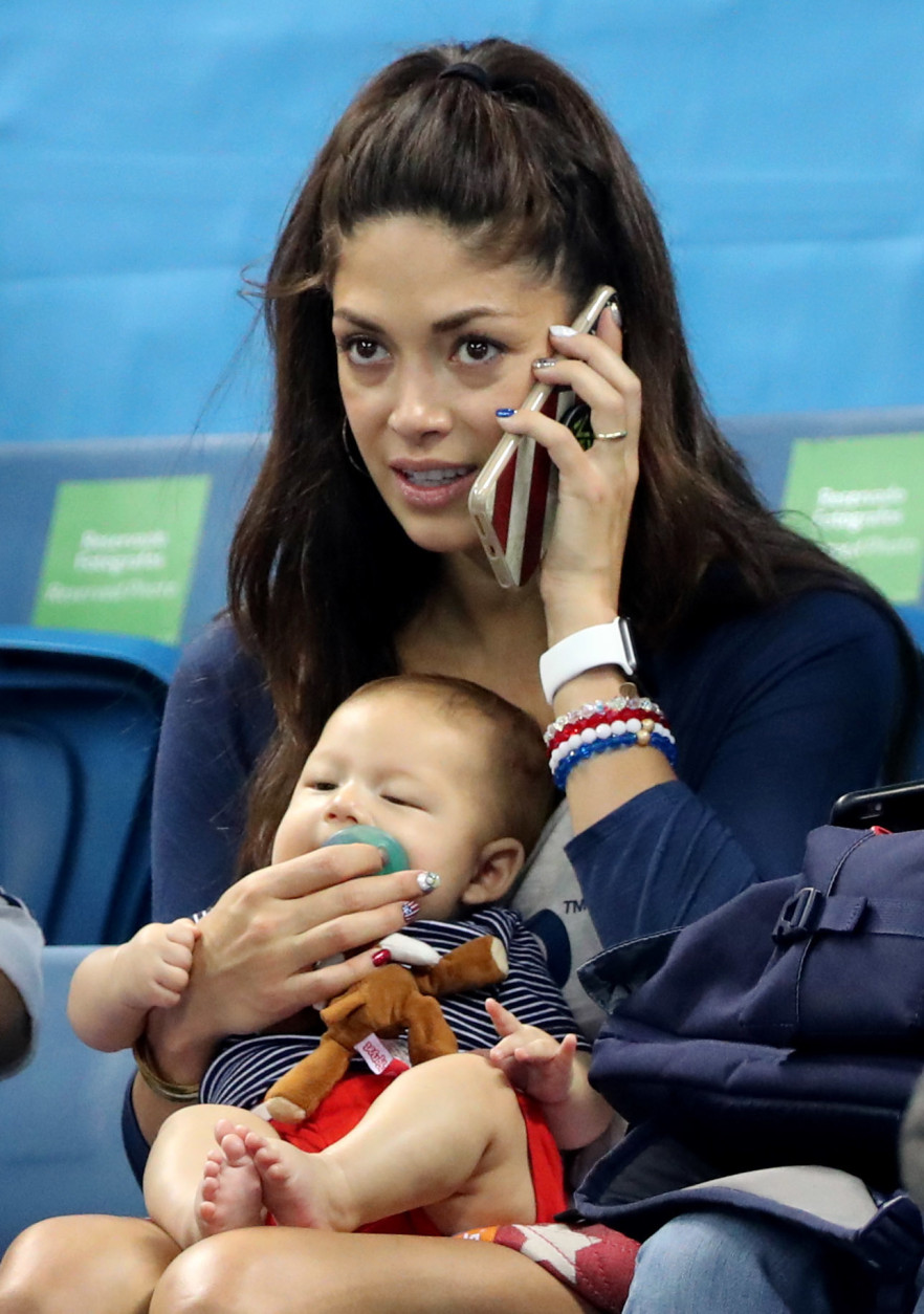 Nicole Johnson, fiance of United States' Michael Phelps, holds their baby Boomer during the swimming competitions at the 2016 Summer Olympics, Monday, Aug. 8, 2016, in Rio de Janeiro, Brazil. (AP Photo/Lee Jin-man)