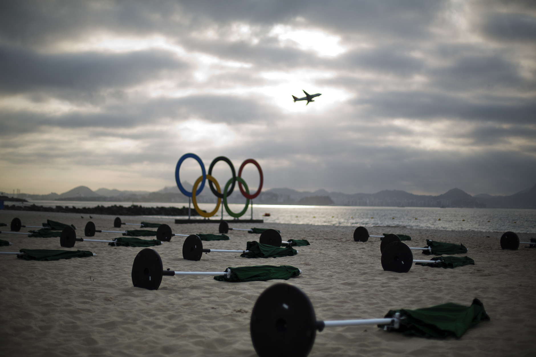 Umbrellas lay on the sand at the sailing venue as a plane takes off in the distance at the 2016 Summer Olympics in Rio de Janeiro, Brazil, Tuesday, Aug. 9, 2016. (AP Photo/David Goldman)