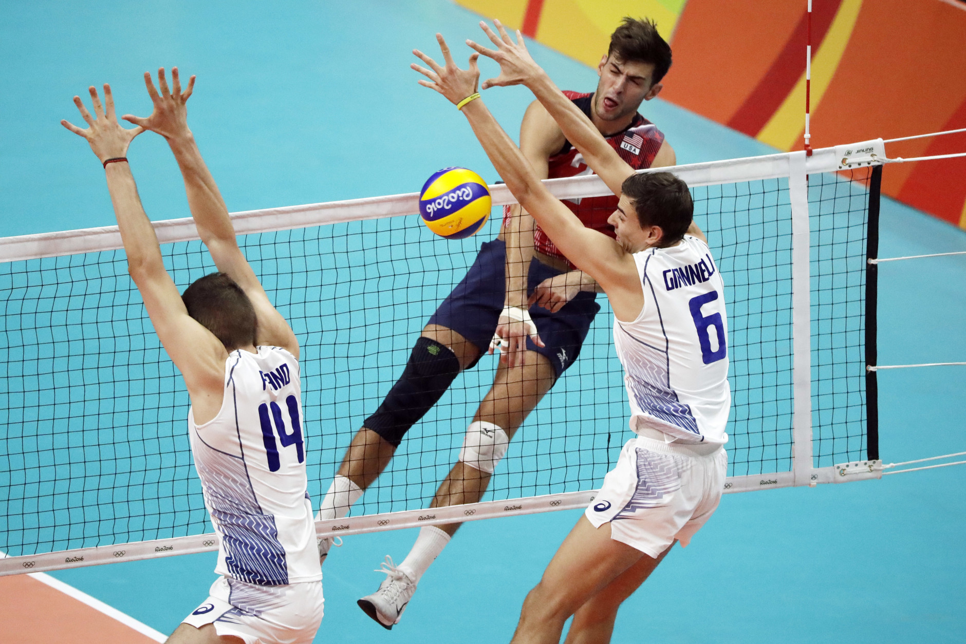 United States' Aaron Russell, top right, spikes the ball as Italy's Simone Giannelli (6) and Matteo Piano block during a men's preliminary volleyball match at the 2016 Summer Olympics in Rio de Janeiro, Brazil, Tuesday, Aug. 9, 2016. (AP Photo/Matt Rourke)
